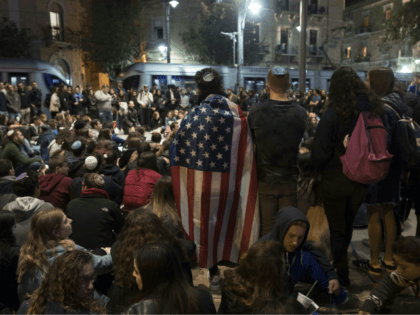 An Israeli man holds the US flag as youths gather in center Jerusalem on October 28, 2018, during a tribute to the victims of a shooting in a Pittsburgh synagogue. - Israeli Prime Minister Benjamin Netanyahu on October 28 expressed grief and solidarity with the United States, after a gunman …
