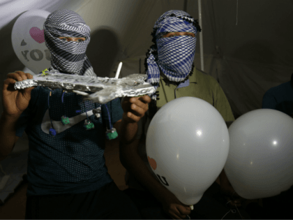 Masked Palestinian protesters calling themselves the 'night confusion units' hold incendiary devices attached to ballons to be flown towards Israel, near the Gaza-Israel border east of Rafah in the southern Gaza Strip, on September 26, 2018. - The border protests since March 30 have been labelled the 'Great March of …