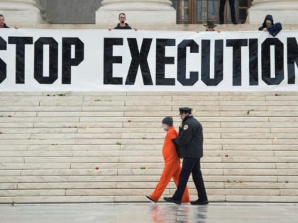 Police remove a man named Randy Gardner who is wearing his executed brother's prison jumpsuit during a protest against the death penalty outside the US Supreme Court in Washington, in January 2017