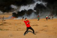 A Palestinian protester uses a slingshot to throw a rock at Israeli forces along the Israel-Gaza border east of Gaza city on October 12, 2018