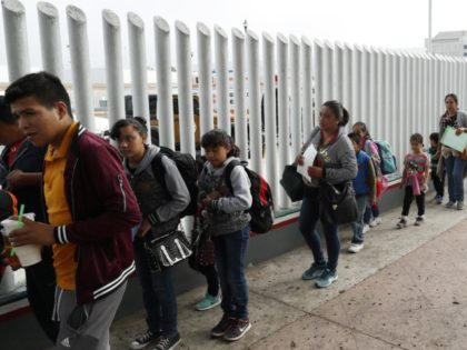 "This July 26, 2018, file photo shows people lining up to cross into the United States to begin the process of applying for asylum near the San Ysidro port of entry in Tijuana, Mexico. Homeland Security's watchdog says immigration officials were not prepared to manage the consequences of its ""zero …"