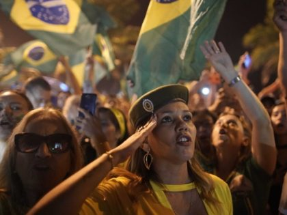 A supporter of Jair Bolsonaro salutes during a celebration in front of his residence after supporters learning he was declared the winner of the election runoff, in Rio de Janeiro, Brazil, Sunday, Oct. 28, 2018 . Brazil's Supreme Electoral Tribunal declared the far-right congressman the next president of Latin America's …