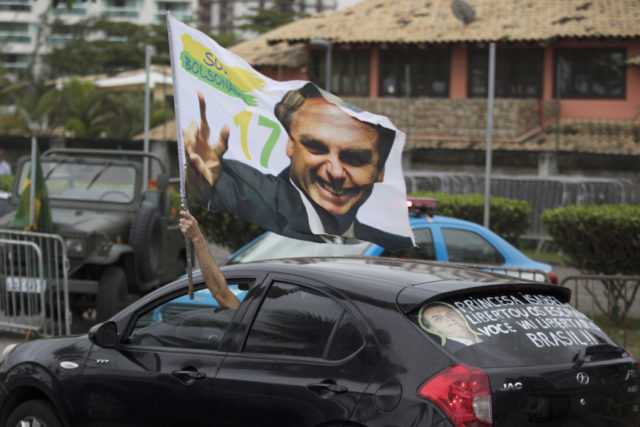 A supporter waves a flag with an image of Jair Bolsonaro as he drives past in front of his residence in Rio de Janeiro, Brazil, Monday, Oct. 29, 2018. Far-right congressman Bolsonaro won Brazil's presidency Sunday on promises to overhaul several aspects of Latin America's largest nation. (AP Photo/Leo Correa)