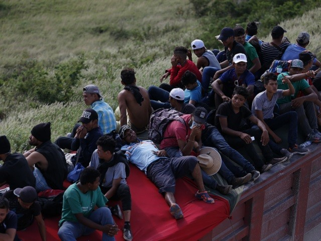 Migrants hitch a ride on the back of a truck as a thousands-strong caravan of Central Americans hoping to reach the U.S. border moves onward from Juchitan, Oaxaca state, Mexico, Thursday, Nov. 1, 2018. Thousands of migrants resumed their slow trek through southern Mexico on Thursday, after attempts to obtain …