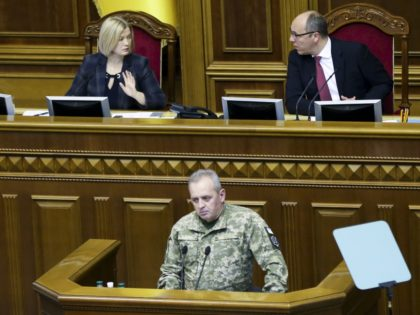Chairman of the Ukrainian General Staff Viktor Muzhenko, bottom, speaks during a parliament session in Kiev, Ukraine, Monday, Nov. 26, 2018. Ukrainian President Petro Poroshenko has halved his proposal for martial law in the country to 30 days, an apparent concession to opponents. (AP Photo/Efrem Lukatsky)