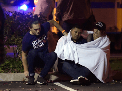 """People comfort each other as they sit near the scene Thursday, Nov. 8, 2018, in Thousand Oaks, Calif. where a gunman opened fire Wednesday inside a country dance bar crowded with hundreds of people on """"college night,"""" wounding 11 people including a deputy who rushed to the scene. Ventura County …"""