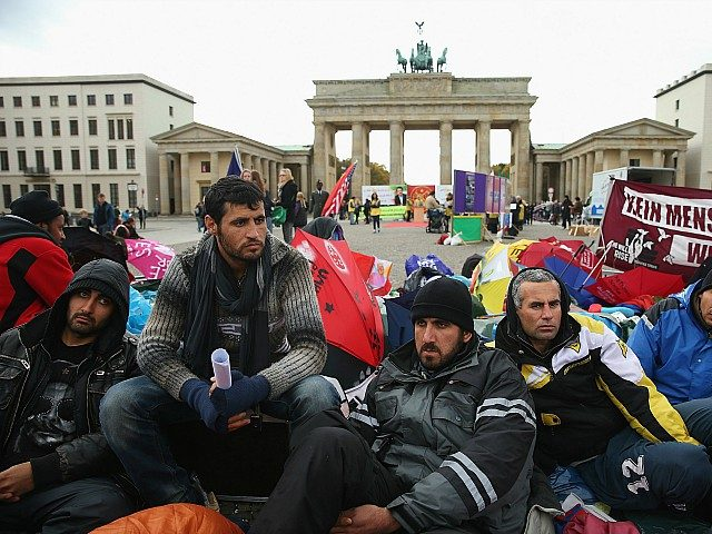 BERLIN, GERMANY - OCTOBER 17: Refugees from Iraq, Iran and Afghanistan keep warm on the 8th day of a hunger strike in front of the Brandenburg Gate on October 17, 2013 in Berlin, Germany. 28 refugees, some of whom have been in Germany for as long as seven years waiting …