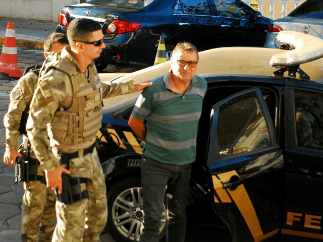 Italian ultra-leftist militant Cesare Battisti arrives escorted by police to the headquarters of the Federal Police in Corumba, Mato Grosso do Sul State, West of Brazil, on October 5, 2017, after a federal judge ordered his preventive detention. Brazilian police on on the eve detained Battisti, who was convicted of …
