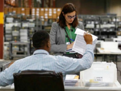 Employees at the Palm Beach County Supervisor of Elections office sort ballot pages during a recount on Wednesday, Nov. 14, 2018, in West Palm Beach, Fla. (AP Photo/Brynn Anderson)