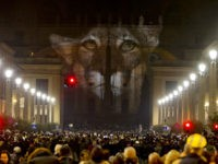 People gather to watch images projected on the facade of St. Peter's Basilica, at the Vatican, Tuesday, Dec. 8, 2015. The Vatican is lending itself to environmentalism with a special public art installation timed to coincide with the final stretch of climate negotiations in Paris. On Tuesday night, the facade …