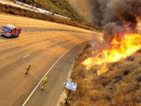 Firefighters work to contain fires at Rocky Peak Mtwy, on state Freeway 118, Monday, Oct. 27, 2003, in Simi Valley, Calif. The 80,000-acre blaze in suburban Simi Valley, 35 miles northwest of Los Angeles, jumped the highway and came within yards of several homes before firefighters began to get the …