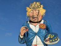 The Edenbridge Bonfire Society's 2018 'Celebrity Guy', former British foreign secretary Boris Johnson, created by artist Andrea Deans, is seen during the unveiling in Edenbridge, Southern England on October 31, 2018. - The giant effigy of Boris Johnson, depicted eating a piece of EU-themed cake wearing his trademark boarding shorts …