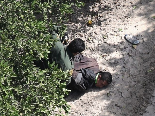 MCALLEN, TX - NOVEMBER 06: U.S. Border Patrol agent detains an undocumented immigrant on November 6, 2018 in McAllen, Texas. Border Patrol agents on the ground, assisted by a helicopter unit of U.S. Air and Marine Operations agents, apprehended a group of immigrants who had crossed the border illegally from …