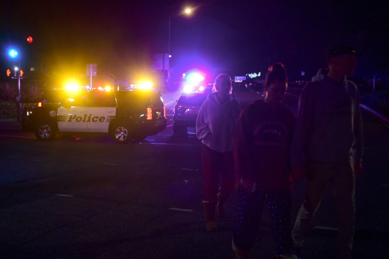 People walk away from the scene as it unfurls at the intersection of US 101 freeway and the Moorpark Rad exit as police vehicles close off the area responding to a shooting at a bar in Thousand Oaks, California on November 8, 2018. - Twelve people, including a police sergeant, were shot dead in a shooting at a night club close to Los Angeles, police said Thursday. All the victims were killed inside the bar in the suburb of Thousand Oaks late on Wednesday, including the officer who had been called to the scene, Sheriff Geoff Dean told reporters. The gunman was also dead at the scene, Dean added. The bar was hosting a college country music night. (Photo by Frederic J. BROWN / AFP) (Photo credit should read FREDERIC J. BROWN/AFP/Getty Images)
