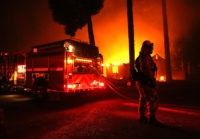 PARADISE, CA - NOVEMBER 08: Firefighters try to save a building as the Camp Fire moves through the area on November 8, 2018 in Paradise, California. Fueled by high winds and low humidity, the rapidly spreading wildfire has ripped through the town of Paradise, charring 18,000 acres and destroying dozens …