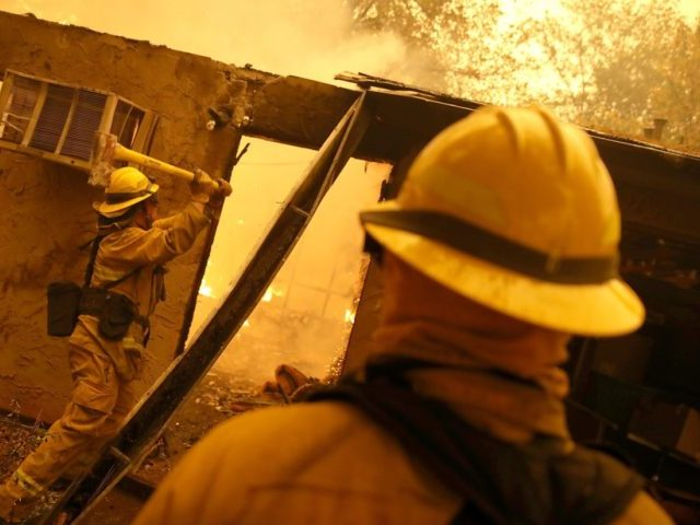 PARADISE, CA - NOVEMBER 09: Firefighters try to keep flames from burning home from spreading to a neighboring apartment complex as they battle the Camp Fire on November 9, 2018 in Paradise, California. Fueled by high winds and low humidity, the rapidly spreading Camp Fire ripped through the town of …