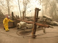 TOPSHOT - CalFire firefighter Scott Wit surveys burnt out vehicles near a fallen power line on the side of the road after the Camp fire tore through the area in Paradise, California on November 10, 2018. - Firefighters in California on November 10 battled raging blazes at both ends of …