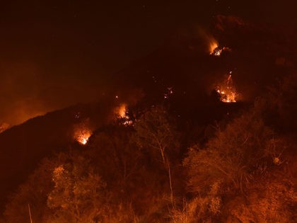 Spot fires burn on the hills above Pepperdine University during the Woolsey fire, November 12, 2018 in Malibu, California. - Another three firefighters have been injured battling the Woolsey Fire, which has devoured mansions and mobile homes alike in the coastal celebrity resort of Malibu, while the death toll from …