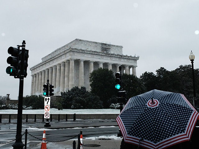 A man uses an umbrella in front of Lincoln Memorial during the year's first snowfall in Washington, DC, on November 15, 2018. (Photo by MANDEL NGAN / AFP) (Photo credit should read MANDEL NGAN/AFP/Getty Images)