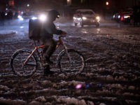 A man rides a bicycle through snow in New York on November 15, 2018 . - The National Weather Service is predicting snowfall totals of 2 to 4 inches in New York City. (Photo by Don EMMERT / AFP) (Photo credit should read DON EMMERT/AFP/Getty Images)