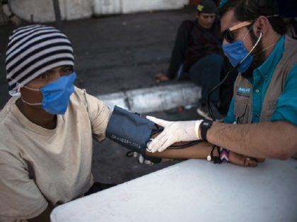 A health staffer checks the blood pressure of a Central American migrant, moving towards the United States in hopes of a better life, in the street in Mexicali, Baja California state, Mexico, on November 16, 2018. - The Central American migrant caravan faced a desperate situation Friday as its numbers …