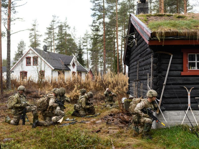 "ELVAL, NORWAY - NOVEMBER 03: British soldiers from Anzio Company of the Duke of Lancaster Regiment take cover from enemy fire behind a log cabin, during the live exercise on November 3, 2018 in Elval, Norway. Over 40,000 participants from 31 nations are taking part in the NATO ""Trident Juncture"" …"