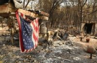An American flag hangs at a burned out mobile home park in Paradise, California on November 18, 2018. - The family lost a home in the same spot to a fire 10 years prior. (Photo by Josh Edelson / AFP) (Photo credit should read JOSH EDELSON/AFP/Getty Images)