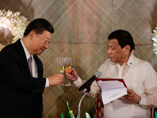 "Chinese President Xi Jinping (L) and Philippines' President Rodrigo Duterte (R) raise a toast during a state banquet at the Malacanang Presidential Palace in Manila on November 20, 2018. - Chinese President Xi Jinping called his visit on November 20 to long-time US ally the Philippines a ""milestone"", as he …"