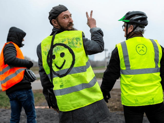 A man gestures next to a bridge over the N70 road on November 23, 2018, near Montceau-les-Mines, central France, as part of nationwide movement called the 'yellow vests' ('gilets jaunes' in French) against high fuel prices which has mushroomed into a widespread protest against stagnant spending power. - A national …