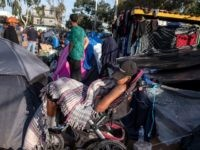 Central American migrants wanting to reach the United States, rest at a temporary shelter in Tijuana, Baja California State, Mexico, near the US-Mexico border fence, on November 23, 2018. - After a trek of more than a month from Honduras, nearly 5,000 migrants have been living in a makeshift shelter …