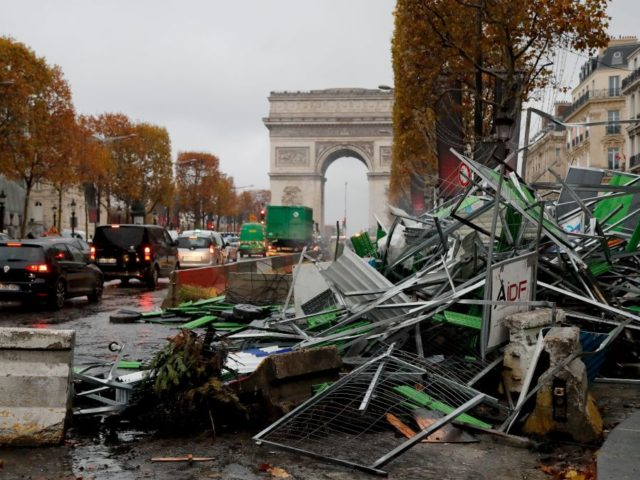 TOPSHOT - A picture taken on November 25, 2018 near the Arc de Triomphe on the Champs-Elysees avenue in Paris shows broken barriers a day after a rally by yellow vest (Gilets jaunes) protestors against rising oil prices and living costs. - Security forces in Paris fired tear gas and …