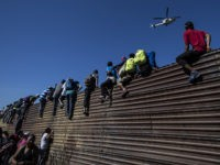 TOPSHOT - A group of Central American migrants -mostly Hondurans- climb a metal barrier on the Mexico-US border near El Chaparral border crossing, in Tijuana, Baja California State, Mexico, on November 25, 2018. - US officials closed the San Ysidro crossing point in southern California on Sunday after hundreds of …