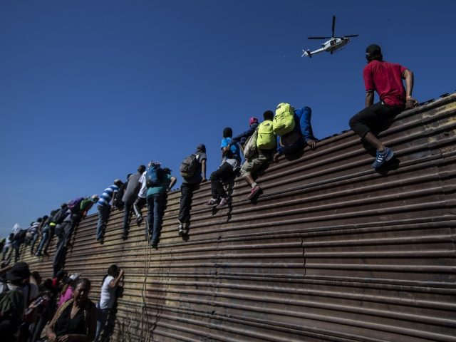 A group of Central American migrants -mostly Hondurans- climb a metal barrier on the Mexico-US border near El Chaparral border crossing, in Tijuana, Baja California State, Mexico, on November 25, 2018. - US officials closed the San Ysidro crossing point in southern California on Sunday after hundreds of migrants, part …