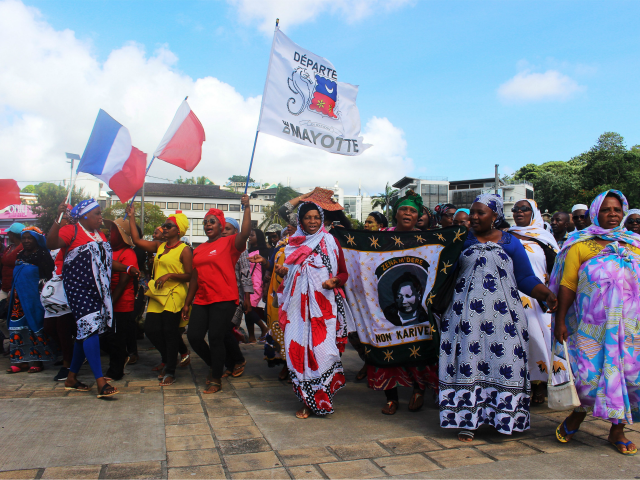 Protesters hold French and Mayotte flags as they gather on the Place de la Republique in Mamoutzou, on the French Indian Ocean island of Mayotte, on March 13, 2018, during a demonstration against insecurity and immigration. The French government attempted on March 12 to end weeks of unrest on the …