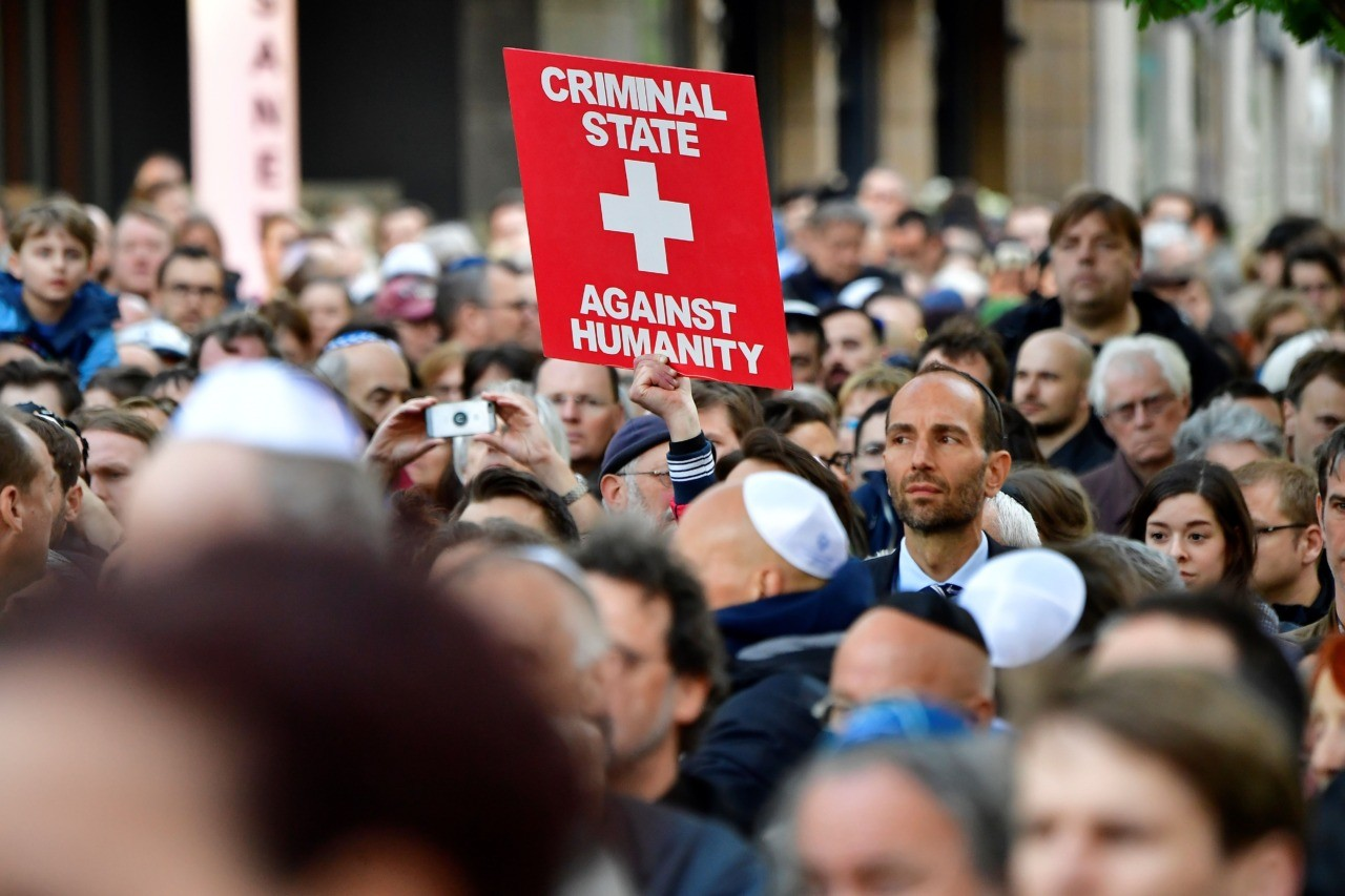 "A protester holds a placard during the ""Berlin wears kippa"" event, with more than 2,000 Jews and non-Jews wearing the traditional skullcap to show solidarity with Jews on April 25, 2018 in Berlin after Germany has been rocked by a series of anti-Semitic incidents. - Germans stage shows of solidarity with Jews after a spate of shocking anti-Semitic assaults, raising pointed questions about Berlin's ability to protect its burgeoning Jewish community seven decades after the Holocaust. (Photo by Tobias SCHWARZ / AFP) (Photo credit should read TOBIAS SCHWARZ/AFP/Getty Images)"