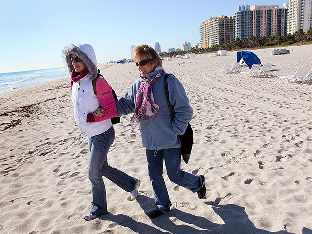 MIAMI BEACH, FL - JANUARY 11: Helena Anderson (L) and her mother Daniela Birska wear jackets as they walk on the beach on January 11, 2010 in Miami Beach, Florida. The National Weather Service said it recorded 36 degrees in Miami Monday morning, which beat the 82-year-old record of 37 …