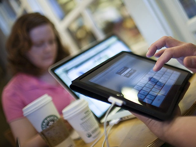 FORT WORTH, TEXAS - APRIL 3: Jamie Phelps, 29, syncs his newly purchased iPad while visiting a Starbucks Coffee with his wife, Ann Phelps, April 3, 2010 in Fort Worth, Texas. Debuting today, the much heralded iPad looks to be a bridge between a laptop and smartphone. (Photo by Tom …