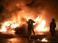 TOPSHOT - Firefighters work to put out a fire as cars burn in the Le Breil neighborhood of Nantes early on July 7, 2018. - A French policeman who shot dead a young black man in western France earlier this week, sparking four nights of rioting, has been charged with …