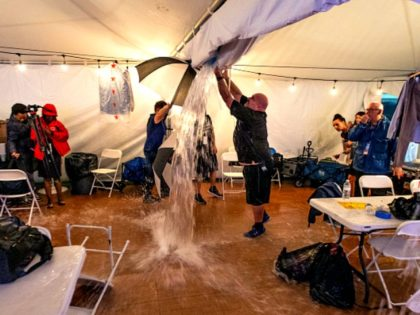 TALLAHASSEE, FL - NOVEMBER 06: One of the members of the media cuts a whole in the ceiling of the press tent as they evacuated the media just before the start of Florida Democratic gubernatorial candidate Andrew Gillum's election night watch party at Florida A&M University on November 6, 2018 …