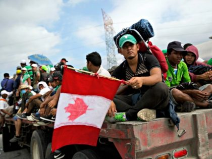 Honduran migrant Fernando Najar Guillen, 22, carries a handmade Canadian flag as he rides on the back of a flatbed truck with other Central Americans, outside Juchitan, Oaxaca state, Mexico, Thursday, Nov. 1, 2018. Najar said he plans to continue across the entire U.S. and seek work in Canada.