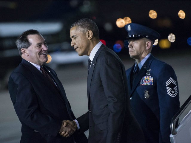 US President Barack Obama (C) is greeted by Senator Joe Donnelly (L), D-IN, at Gary Chicago International Airport October 1, 2014 in Gary, Indiana. Obama will attend a campaign event for Gov. Pat Quinn, D-Il, and deliver remarks on the economy at Northwestern University. AFP PHOTO/Brendan SMIALOWSKI (Photo credit should …