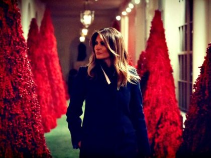Melania Among Red Christmas Trees
