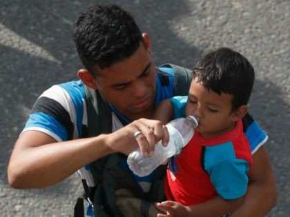 A man carrying a boy gives the child water while walking with a caravan of Central American migrants heading for the U.S., as the group departs Ciudad Hidalgo, Mexico, Sunday, Oct. 21, 2018. Despite Mexican efforts to stop them at the border, about 5,000 Central American migrants resumed their advance …