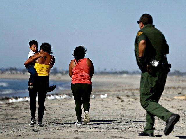 Two women, one carrying a child, walk north after crossing illegally into the United States as a Border Patrol agent moves in to detain them Wednesday, Nov. 14, 2018, seen from Tijuana, Mexico. Migrants in a caravan of Central Americans scrambled to reach the U.S. border, catching rides on buses …