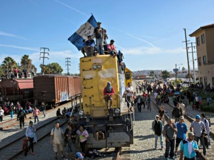 A migrant waves an Honduran flag along the railroad tracks at the Mexico-U.S. border in Tijuana, Mexico, Sunday, Nov. 25, 2018, as a group of migrants tries to reach the U.S. The mayor of Tijuana has declared a humanitarian crisis in his border city and says that he has asked …