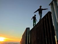 Two Central American migrants walk along the top of the border structure separating Mexico and the United States Wednesday, Nov. 14, 2018, in Tijuana, Mexico. Migrants in a caravan of Central Americans scrambled to reach the U.S. border, catching rides on buses and trucks for hundreds of miles in the …