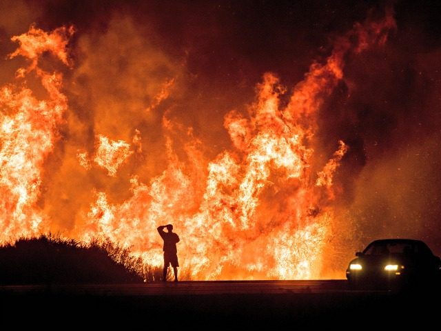 n this Dec. 6, 2017, file photo, a motorist on Highway 101 watches flames from the Thomas Fire, the largest wildfire on record in California, leap above the roadway north of Ventura, Calif. On Thursday, May 10, 2018, Gov. Jerry Brown signed an executive order that aims to reduce the …