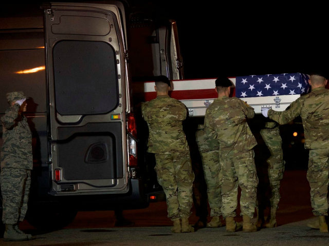 Members of the U.S. military carry a transfer case covered with an American flag during a dignified transfer for Sgt. Leandro Jasso on Nov. 27 in Dover, Del. (Mark Makela/Getty Images)