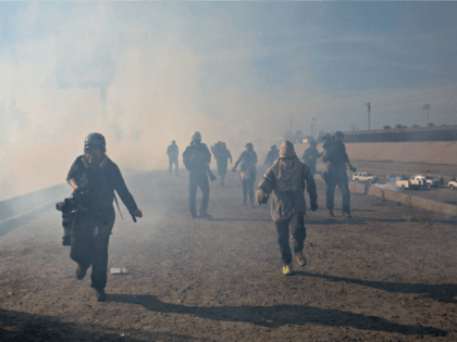Migrants run from tear gas launched by U.S. agents, amid photojournalists covering the Mexico-U.S. border, after a group of migrants got past Mexican police at the Chaparral crossing in Tijuana, Mexico, Sunday, Nov. 25, 2018. The mayor of Tijuana has declared a humanitarian crisis in his border city and says …