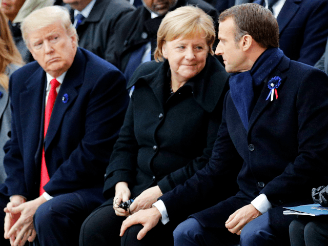 TOPSHOT - French President Emmanuel Macron (R) touches the knee of German Chancellor Angela Merkel (2nd R) as they sit next to US President Donald Trump (2nd L) and US First Lady Melania Trump (L) during a ceremony at the Arc de Triomphe in Paris on November 11, 2018 as …